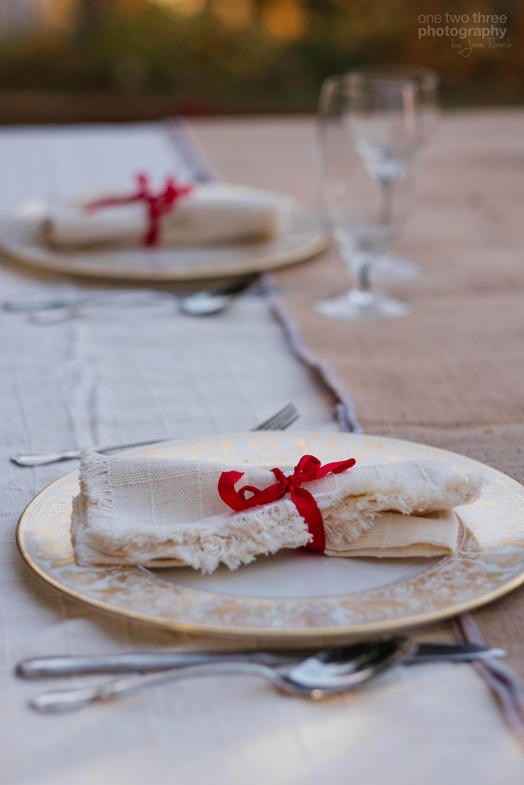 Christmas table place setting with fine china and red ribbon