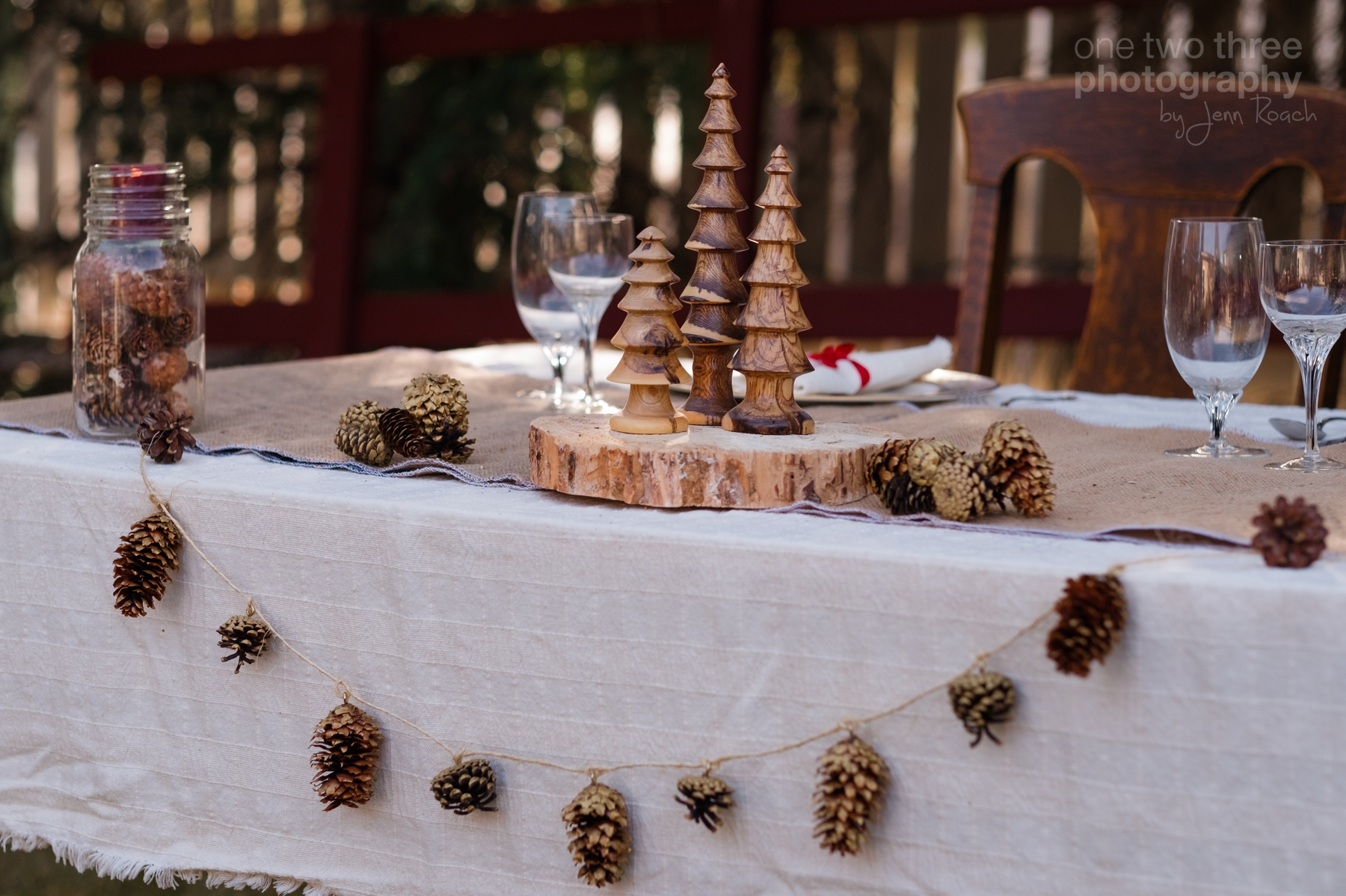 Rustic wedding table settings with pinecones and wood place settings